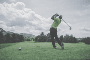 A golfer holding his follow through after hitting a tee shot