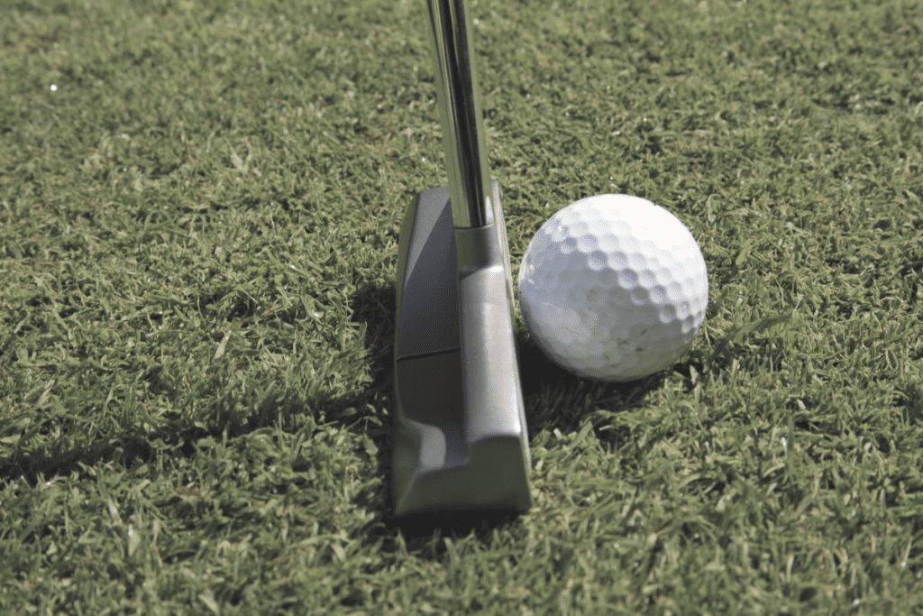 Blade style putter resting behind ball