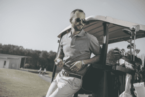 photo of man wearing sunglasses leaning on golf cart