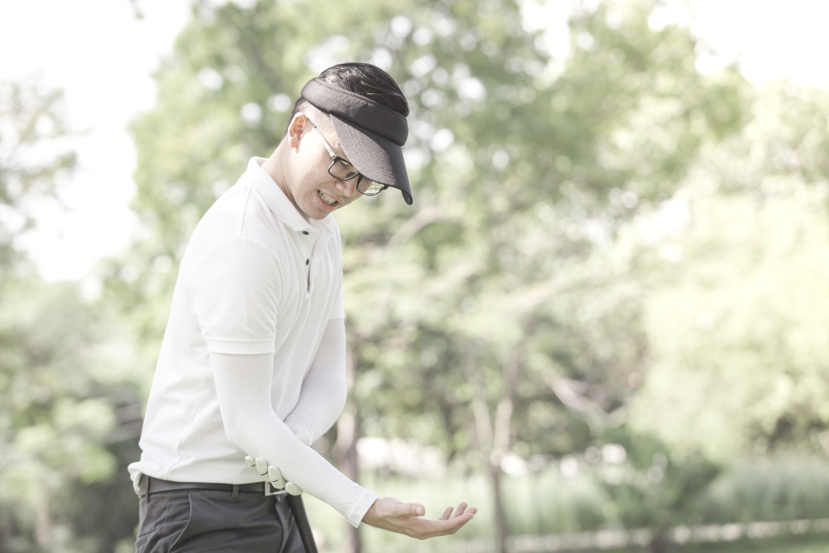 golfer holding elbow in pain