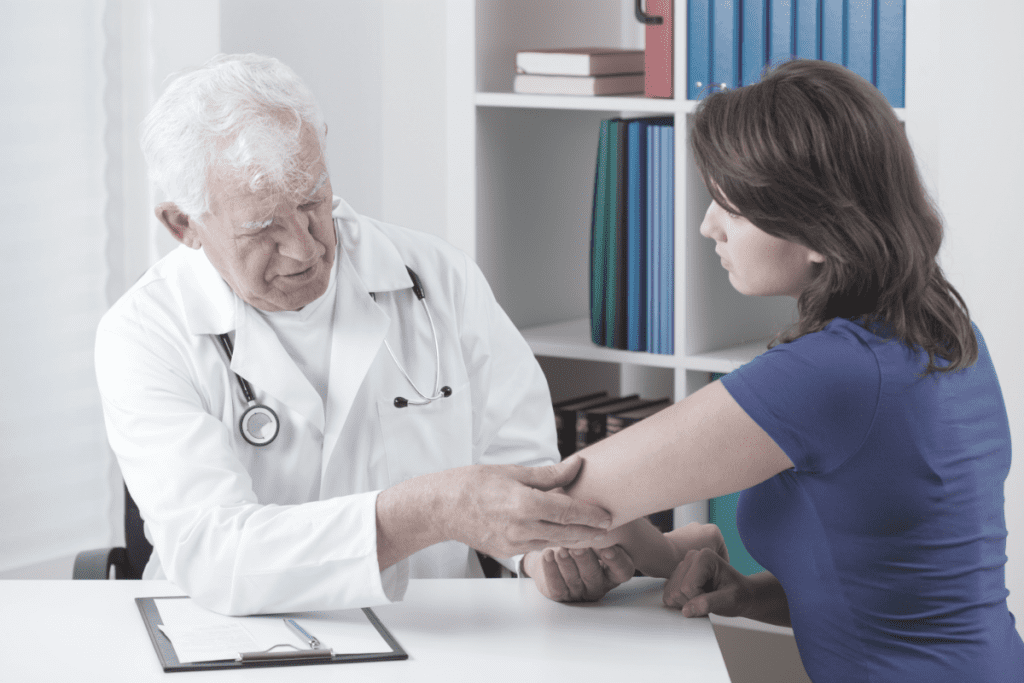 doctor diagnosing a female patients elbow