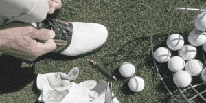 golfer tying golf shoe on driving range