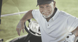 senior golfer sitting in golf cart smiling