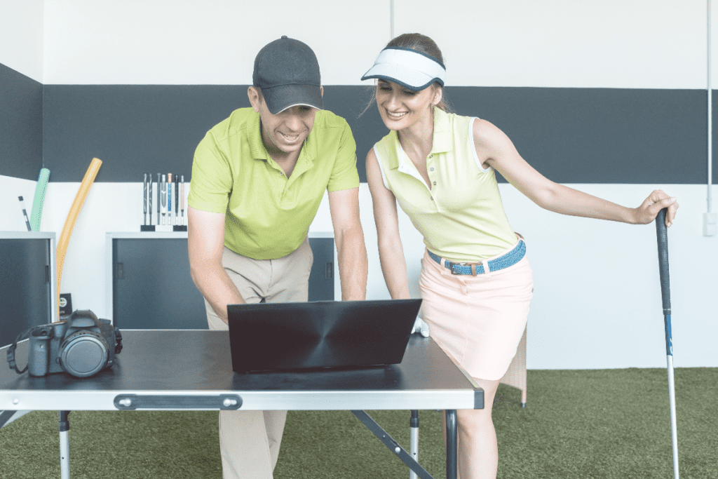 male and female golfers looking at a laptop