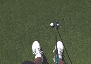 male golfer on putting green looking down