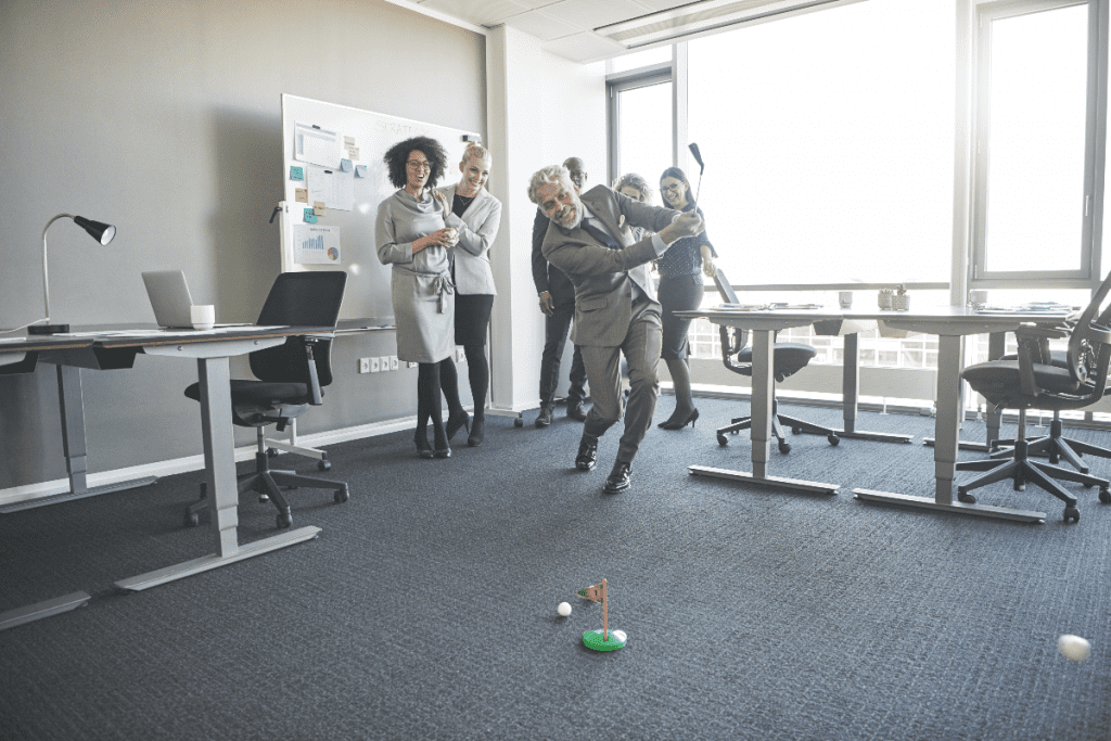 coworkers playing mini golf in office
