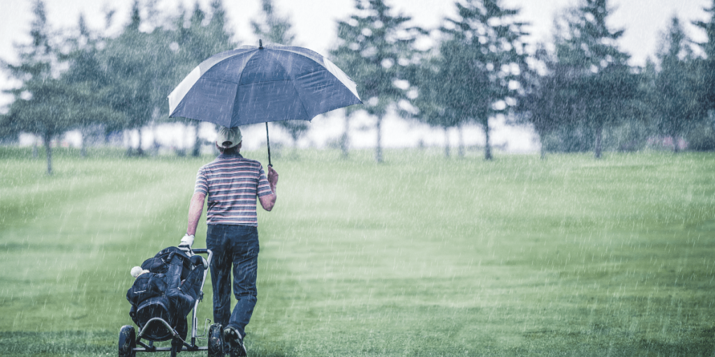man walking on golf course with pull cart and umbrella