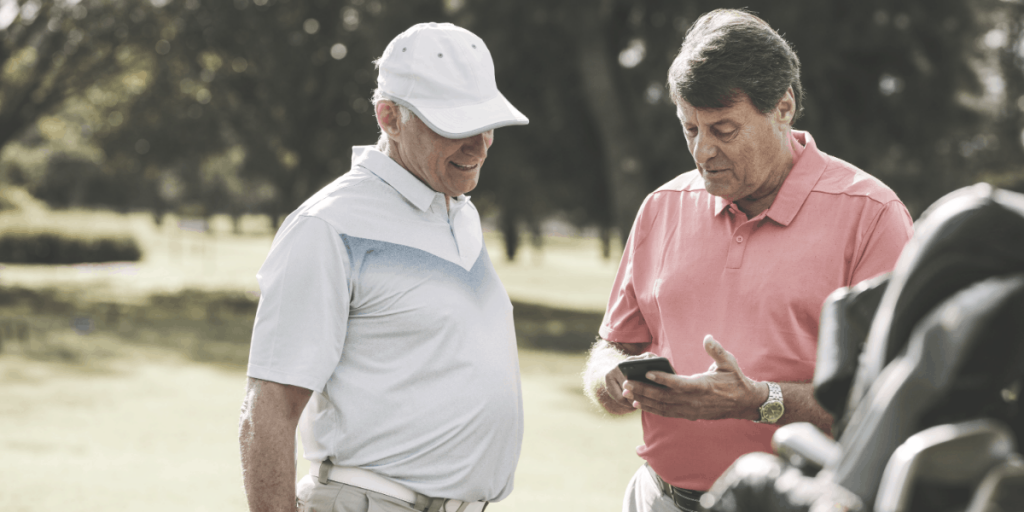 two golfers looking at a handheld device
