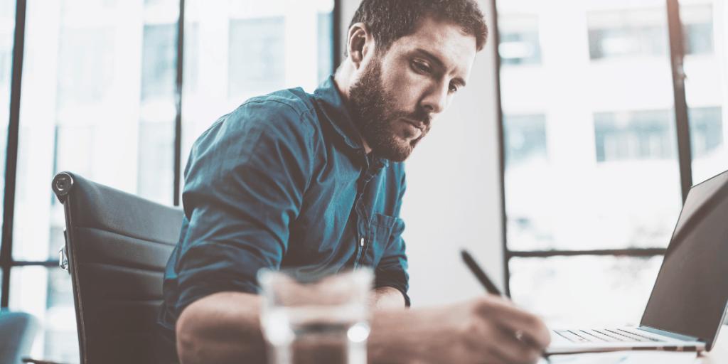 man sitting at desk with laptop analyzing